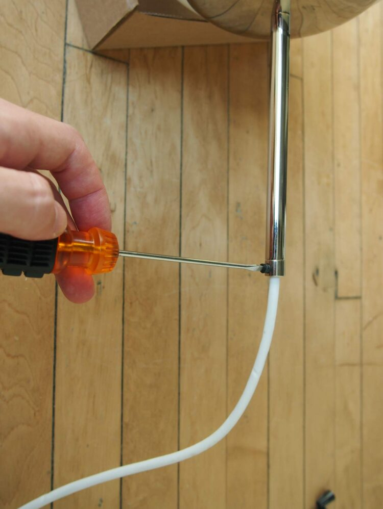 10   Place the neckless ball holder on the ball, tighten the 6in pipe to the threaded nipple and tighten the male threaded strain relief to the 6in pipe. Tighten the plastic screw on the strain relief.