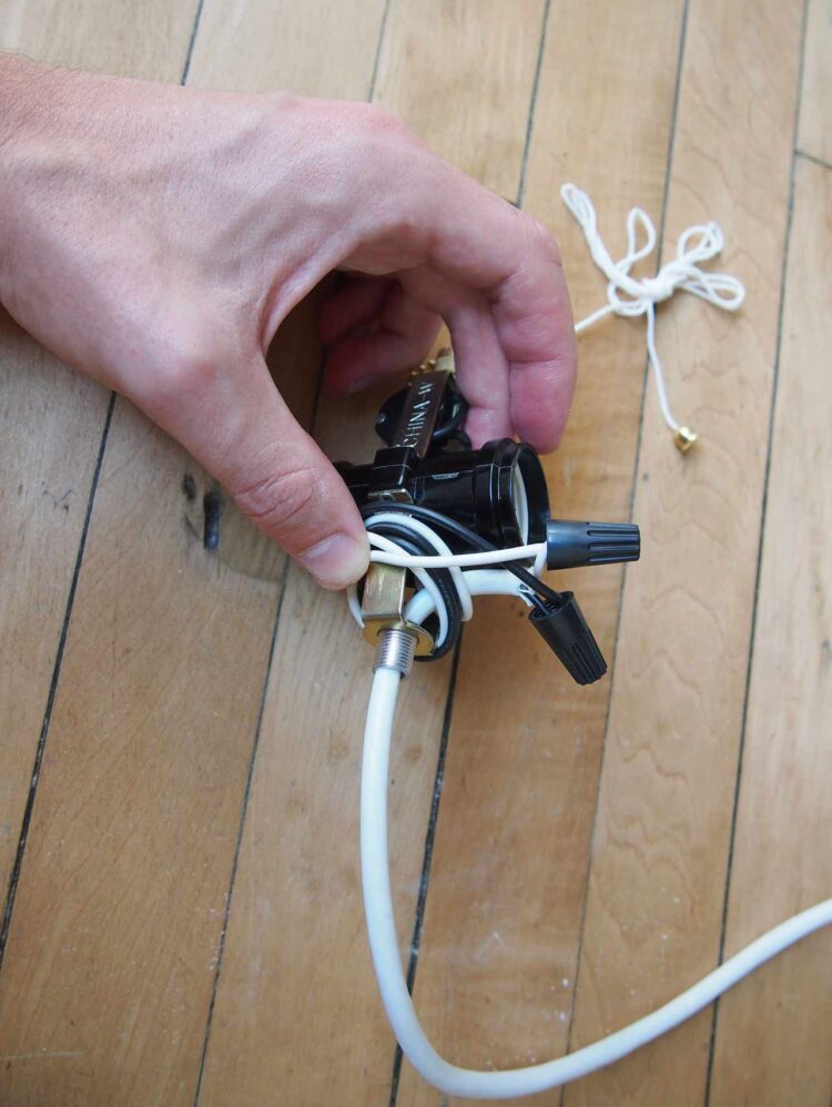 """2   Wrap excess wire around the top of the socket. Match up white """"neutral"""" wires and screw wire nut onto them. Match up black """"hot"""" wires and screw the other wire nut onto them. Make sure no metal wire is exposed. USE CAUTION...Please research how to do this exactly the right way with the socket and cord you have. All parts will be slightly different than those pictured."""