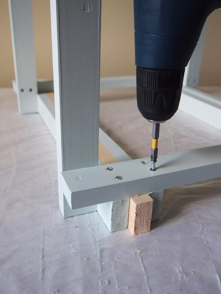 13     Turn the frame over, and using one length of wood as a measuring spacer, secure a piece of wood parallel to the edge of the frame. Drill and screw each end.