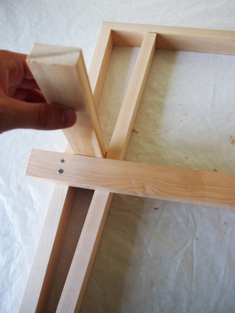 13     Use the width of a spare piece of wood as a spacer, and pinch the two vertical pieces together on the bottom, making sure the ends of the angled pieces are flush with the ends of the straight pieces.