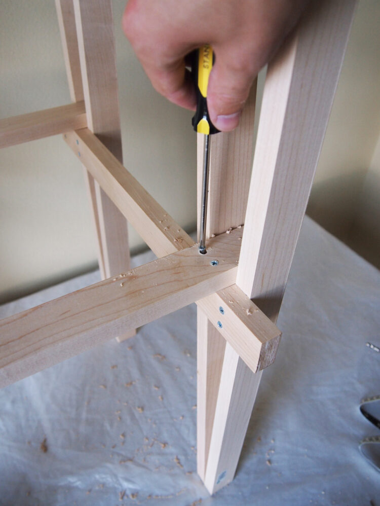 21     Drill vertical holes, countersink, and add two screws to the 20in (50cm) piece, securing it to the 17.75in (45cm) piece. Repeat in 3 other locations to secure the frame.