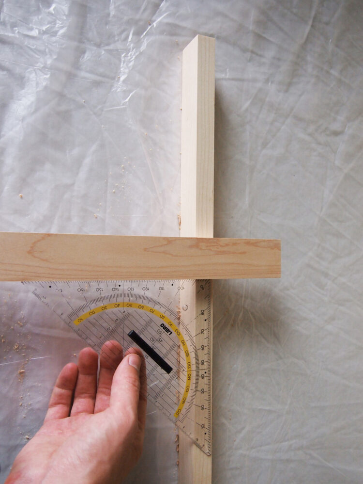 7     On the right side, align the horizontal piece 10in (25.5cm) from the top of the vertical piece. The horizontal piece should extend 2.75in (7cm) beyond the vertical piece. Use a square tool to confirm 90 degree angle.