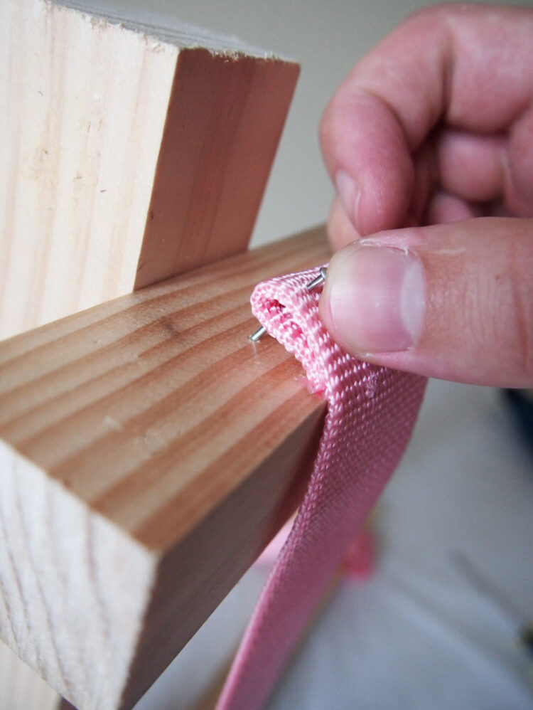 11     Stretch the webbing across the frame, fold the other end of the webbing underneath itself, push a nail through the end, and prepare to drive the nail in. The strap must be very tight on the frame, so use the nail to lever the strap tighter before driving it in.